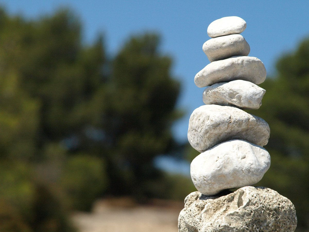 White stones balanced in a pile, with a blue sky background